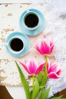 Кофе, круассаны и три красивых розовых тюльпана на старом белом столе