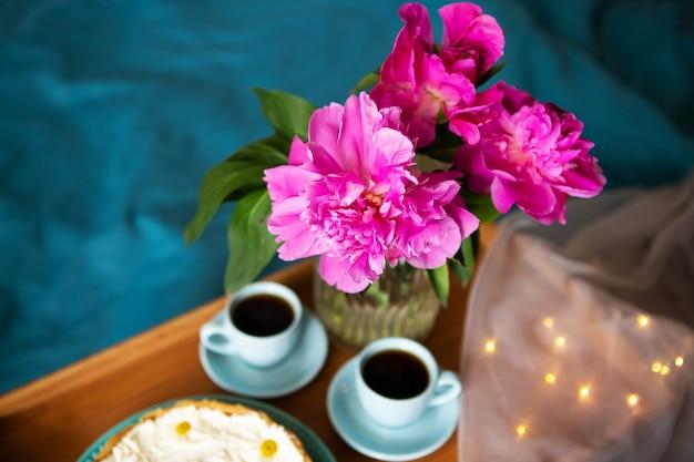 Прекрасное утро ванильный чизкейк, кофе, синие чашки, розовые пионы в стеклянной вазе.