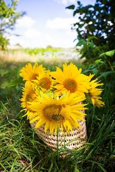 ひまわりの花束は緑の芝生の上のストローバッグにあります。