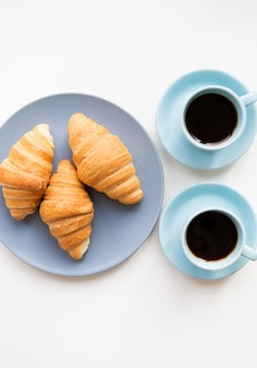 白い背景の上のクロワッサンとコーヒーのカップ