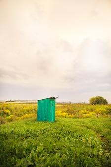 Деревянный туалет с резным окном в форме сердца, открытое поле