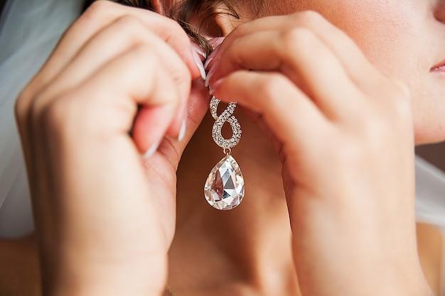 Свадебная невеста вешает золотые серьги с бриллиантом