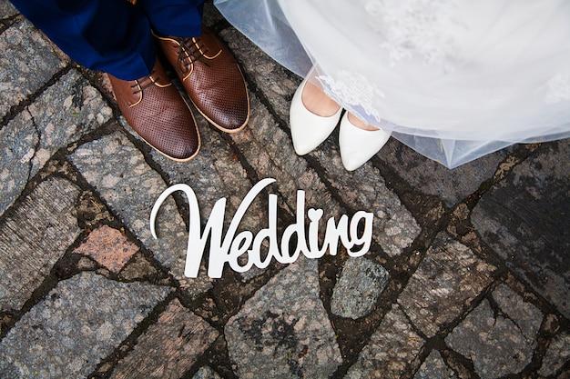 Деревянная вывеска с надписью белой краской свадьбы.ноги молодоженов