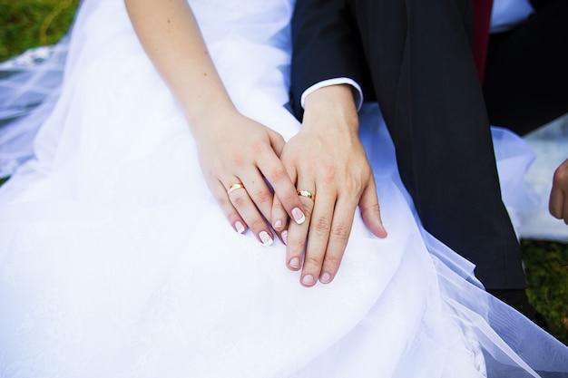 Крупным планом двух рук молодых людей с обручальными кольцами