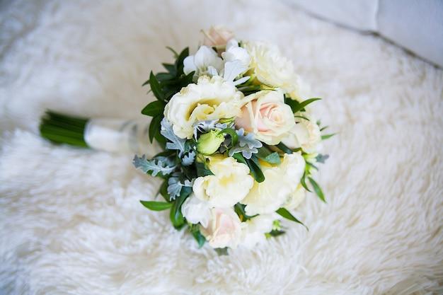 Крупный план красиво оформленного свадебного букета на диване