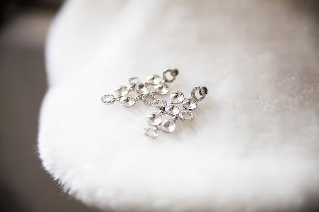 Серьги невесты лежат на белом мысе крупным планом