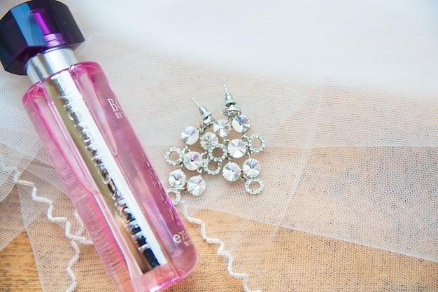 Парфюмерная банка и серебряные серьги невесты крупным планом