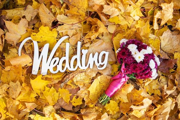 Слово свадьба из дерева на желтых листьях и букет невесты