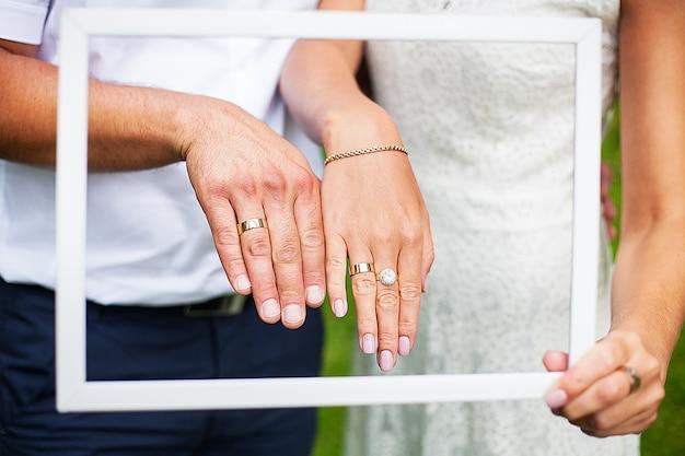 Руки молодоженов показывают свои обручальные кольца