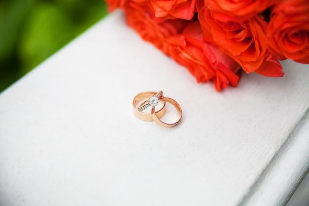美しい結婚指輪と赤いバラの花束