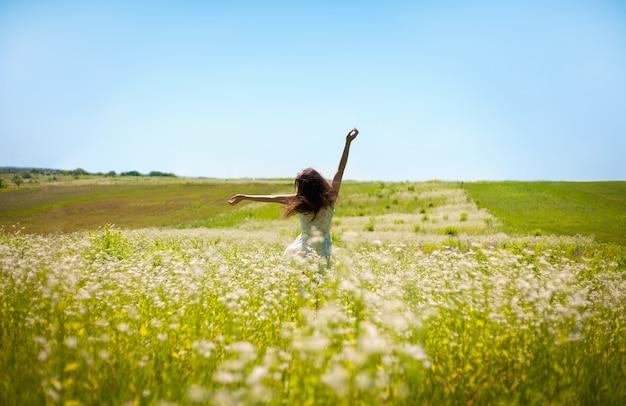空中で彼女の手を持ち上げる少女は、フィールドを横切って走る