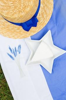 Шляпа, сыр бри в тарелке на синей скатерти