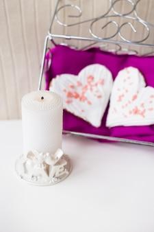 Свеча и печенье в форме сердца на розовой салфетке