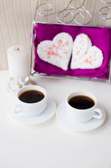 Две чашки кофе, печенье и свеча в форме сердца на розовой салфетке