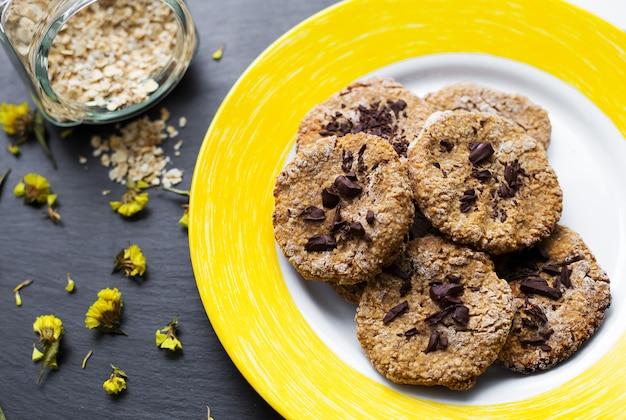 Овсяное печенье с шоколадом на желтой тарелке