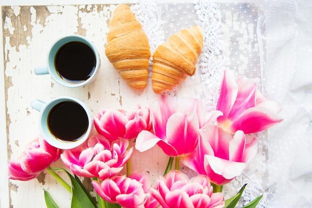 クロワッサン、コーヒー、ピンクのチューリップの花束