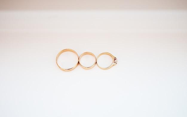 Три обручальные кольца на белом фоне