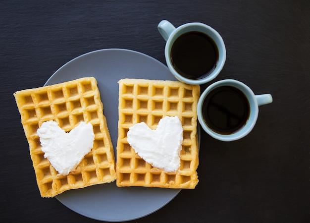 Вкусные бельгийские вафли с кремом на черном фоне и две чашки кофе.