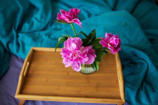 Очень красивый букет пионов в вазе стоит на деревянном подносе на кровати.