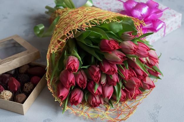 Букет из роз, коробка конфет и подарок для влюбленных