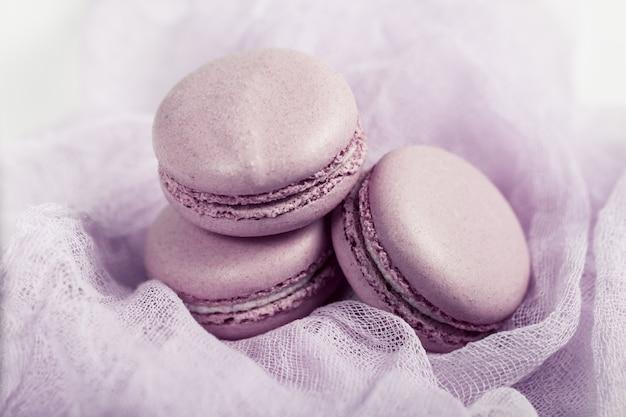 Вкусный французский десерт. три нежных пастельных нежно-розовых пирожных макарон или макаруны на воздушной ткани