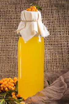 Вегетарианское питание, здоровое питание, сохранение урожая спелой сочной облепихи, приготовление свежего полезного витаминного напитка. бутылка с соком и ветвями апельсина облепихи