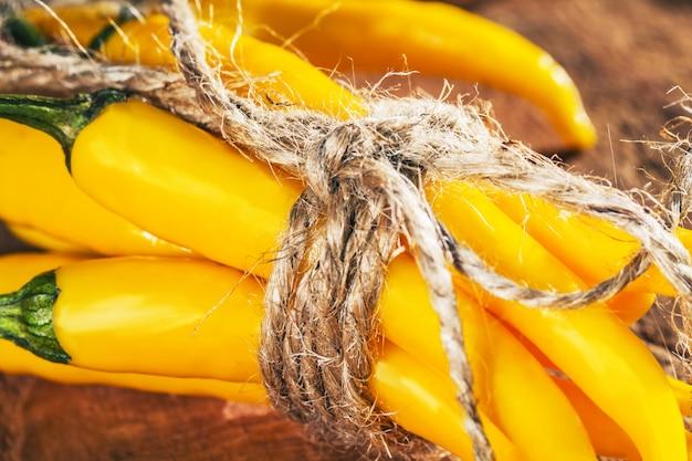 黄色の唐辛子の糸、冬、健康的な食事の概念のためのピーマンの収穫の概念と結ばれる
