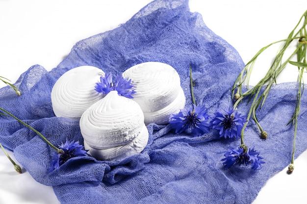 白いロシアのマシュマロゼファー、青いナプキンにヤグルマギクでクローズアップ。ソフトフォファ。