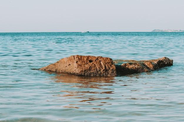 海の小さな岩、トーン、ティール、オレンジ