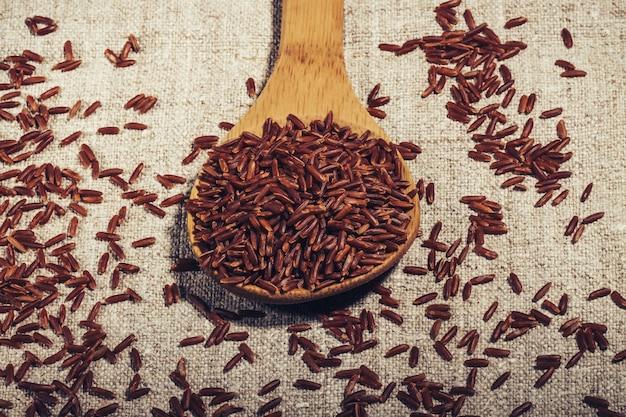 Коричневый рис жасмин в деревянной ложкой на натуральной салфетке крупным планом,