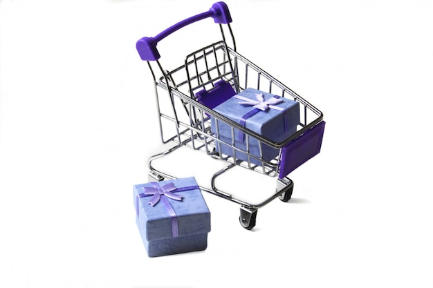 Тележка из супермаркета с подарочными коробками на белом