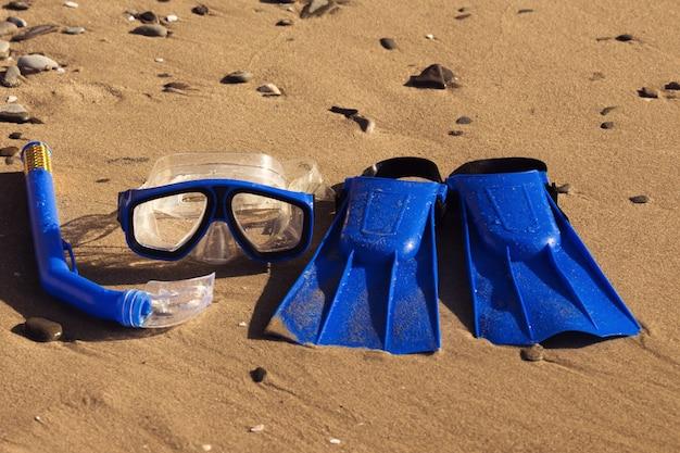 砂浜でのサーフィンのためのブルースイムフリッパー、マスク、シュノーケル。ビーチ