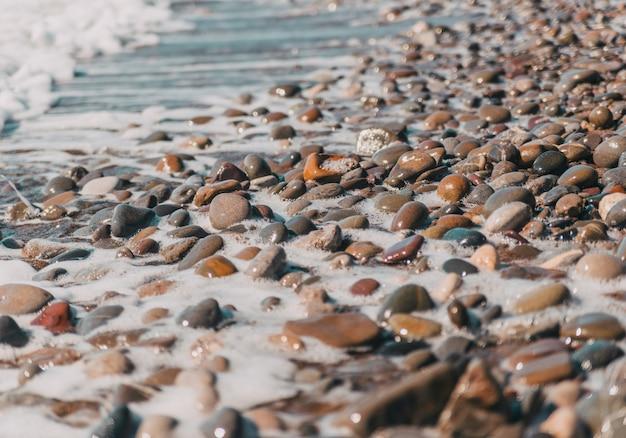 Морская галька омывается волной