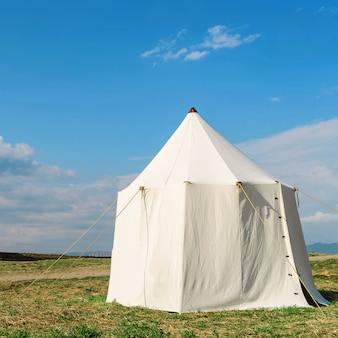 空を背景に芝生の上の白いテント