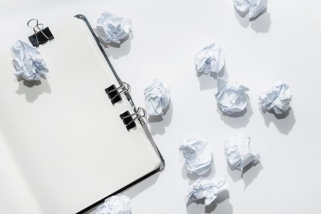 Открыт блокнот на белом с мятой бумаги