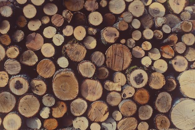 Круглые неразбитые дрова сложены в поленницу