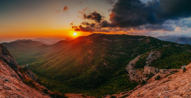 山のパノラマの美しい黄金の夕日