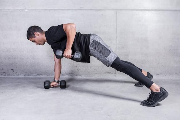 Спортсмен делает упражнения с гантелями