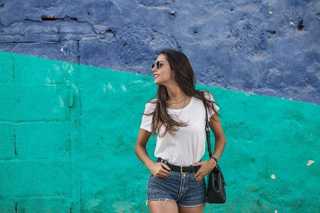 Модная женщина стоит с руками в карманах