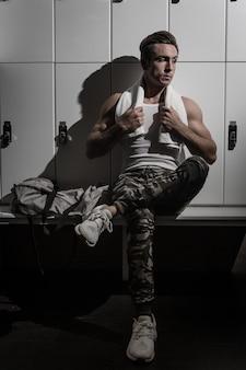 Расслабленный спортсмен сидит возле шкафчиков