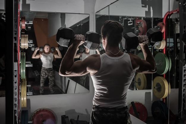 鏡の近くのダンベルを持ち上げる強力な男