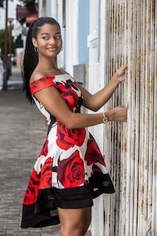立っていると通りに目をそむけるカラフルなドレスで物思いにふける民族女性