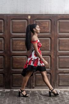 通りを歩いてカラフルなドレスで自信を持って民族の女性