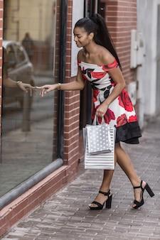 ウィンドウショップでスタイリッシュな民族女性買い物客決定製品