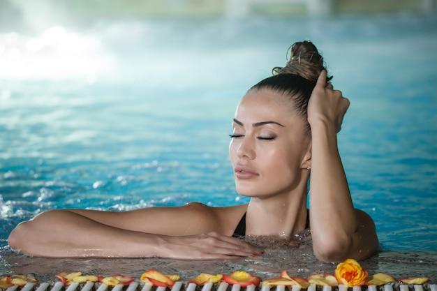 Чувственная женщина трогательно мокрые волосы в бассейне