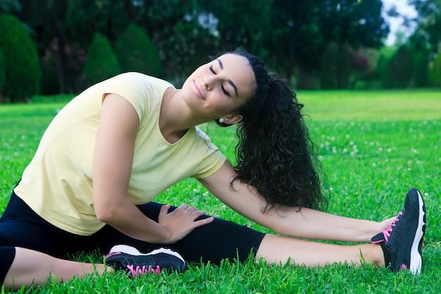 草の上に足を伸ばして笑顔のスポーツウーマン
