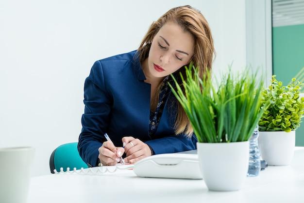 座っているとオフィスで書く女性