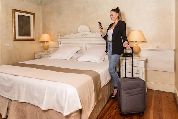 ホテルの部屋でスマートフォンを持つ女性実業家