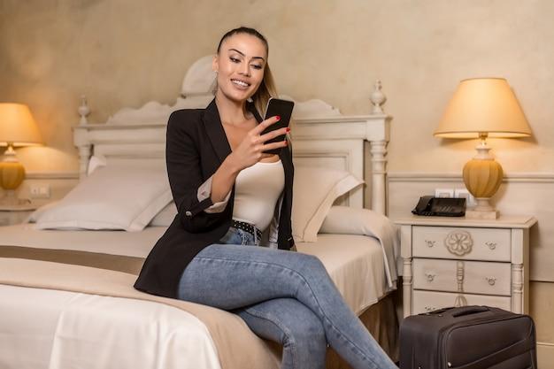 スマートフォンを使用して陽気な若い女性
