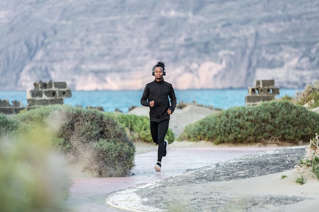 海岸で実行されているヘッドフォンでアフリカ系アメリカ人の運動選手